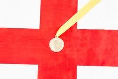 Primo piano della medaglia d'oro sulla bandiera di inglese Fotografie Stock