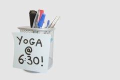 Primo piano della nota appiccicosa con il messaggio di yoga sul supporto della penna sopra fondo bianco Fotografia Stock