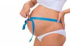 Primo piano della pancia incinta Volume di misurazione di nastro di misurazione della pancia Fotografia Stock