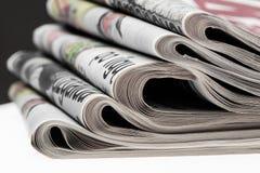Primo piano della pila di giornali Assortimento dei giornali piegati su bianco Ultime notizie, giornalismo, potere dei media, Fotografia Stock Libera da Diritti