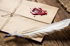 Primo piano della piuma sulla busta con sigillante ed il calamaio rossi Immagine Stock