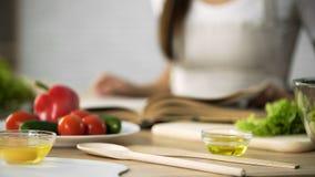 Primo piano della ragazza che lancia through cucinando le pagine del libro, scegliente ricetta dell'insalata immagine stock libera da diritti