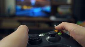 Primo piano della ragazza che tiene una leva di comando e che gioca un video gioco su una TV archivi video