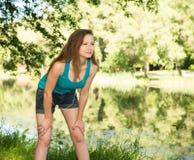 Primo piano della ragazza del corridore all'aperto che riposa sulla banca del lago Fotografie Stock