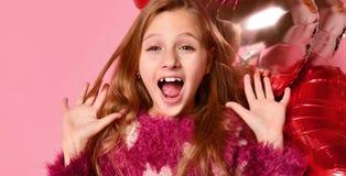 Primo piano della ragazza sveglia in uno studio, sorridente ampiamente e giocante con i palloni rosa Porta il maglione ed i jeans fotografia stock libera da diritti