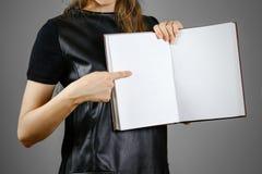 Primo piano della ragazza in vestito nero che tiene il libro bianco aperto dello spazio in bianco sopra Immagine Stock Libera da Diritti