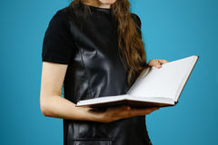 Primo piano della ragazza in vestito nero che tiene il libro bianco aperto dello spazio in bianco sopra Fotografie Stock