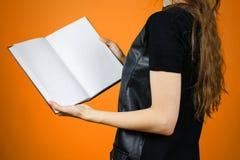 Primo piano della ragazza in vestito nero che tiene il libro bianco aperto dello spazio in bianco sopra Fotografia Stock