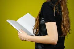 Primo piano della ragazza in vestito nero che tiene il libro bianco aperto dello spazio in bianco sopra Immagini Stock Libere da Diritti
