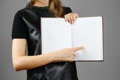 Primo piano della ragazza in vestito nero che tiene il libro bianco aperto dello spazio in bianco sopra Fotografia Stock Libera da Diritti