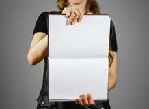 Primo piano della ragazza in vestito nero che tiene il libro bianco aperto dello spazio in bianco sopra Immagine Stock