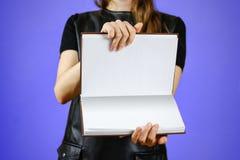 Primo piano della ragazza in vestito nero che tiene il libro bianco aperto dello spazio in bianco sopra Fotografie Stock Libere da Diritti