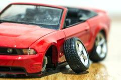 Primo piano della retrovisione dell'automobile rossa del giocattolo dopo l'incidente stradale Fotografie Stock
