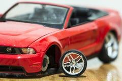 Primo piano della retrovisione dell'automobile rossa del giocattolo dopo l'incidente stradale Immagini Stock Libere da Diritti