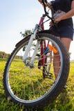 Primo piano della ruota di bicicletta con il ciclista irriconoscibile Fotografia Stock Libera da Diritti