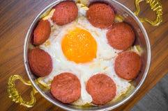 Primo piano della salsiccia turca (sucuk) e dell'uovo fritto in pentola di rame sulla tavola di legno fotografia stock