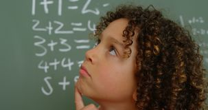 Primo piano della scolara razza mista premurosa con la mano sulla condizione del mento nell'aula a scuola 4k archivi video