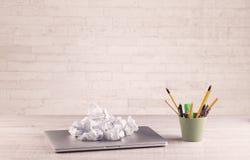Primo piano della scrivania con il muro di mattoni bianco Fotografia Stock