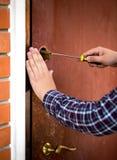 Primo piano della serratura di porta della riparazione del carpentiere con il cacciavite immagine stock libera da diritti