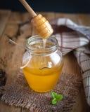 Primo piano della sgocciolatura del miele in un barattolo su fondo di legno fotografie stock libere da diritti