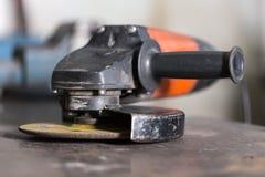 Primo piano della smerigliatrice di angolo che si trova sulla tavola Fotografia Stock