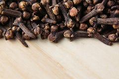 Primo piano della spezia del chiodo di garofano su fondo beige di legno Fotografie Stock