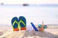 Primo piano della spiaggia di estate con gli accessori dei Flip-flop blu, della crema di protezione del sole, dell'asciugamano e  immagine stock libera da diritti