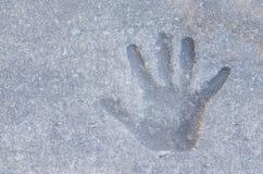 Primo piano della stampa della mano di un bambino in una sabbia del fango del marciapiede concreto Fotografia Stock