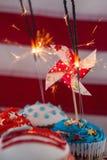 Primo piano della stella filante bruciante sui bigné decorati Immagini Stock