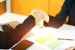 Primo piano della stretta di mano la donna di affari e l'uomo d'affari nel wo Fotografia Stock