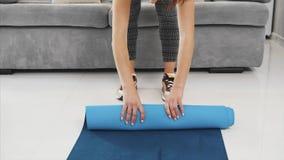 Primo piano della stuoia blu complessa femminile di forma fisica o di yoga dopo lavoro a casa nel salone