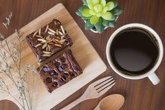 Primo piano della tazza di caffè nero e dei brownie su una tavola di legno fotografia stock libera da diritti
