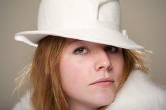 Primo piano della testarossa in cappello di feltro e pelliccia bianchi Fotografia Stock