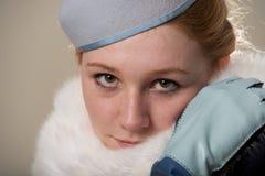 Primo piano della testarossa in cappello di feltro e pelliccia blu Fotografia Stock