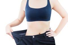 Primo piano della vita esile della giovane donna in grandi jeans che mostrano riuscita perdita di peso, isolata su fondo bianco Immagini Stock Libere da Diritti
