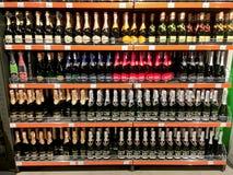 Primo piano delle bottiglie di vino sugli scaffali nel supermercato Fotografie Stock