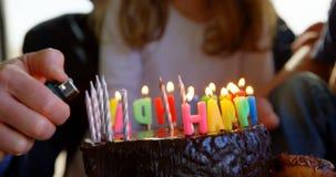 Primo piano delle candele di prima generazione di illuminazione sulla torta di compleanno 4k stock footage