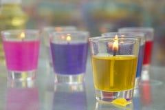 Primo piano delle candele gialle e rosse in supporti di vetro Fotografie Stock