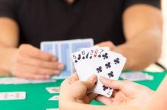 Primo piano delle carte da gioco delle mani che tengono piattaforma Fotografie Stock Libere da Diritti
