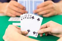 Primo piano delle carte da gioco delle mani che tengono piattaforma Fotografia Stock