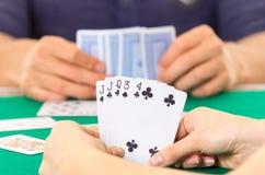 Primo piano delle carte da gioco delle mani che tengono piattaforma Immagini Stock Libere da Diritti