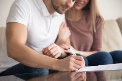 Primo piano delle carte di firma delle giovani coppie felici, acquisto della proprietà, Immagini Stock