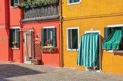 Primo piano delle case variopinte e delle porte con il panno in Burano Fotografie Stock