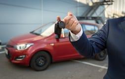 Primo piano delle chiavi dell'automobile della tenuta del capo vendite contro la nuova automobile Fotografia Stock