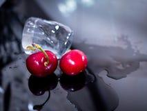 Primo piano delle ciliege e del ghiaccio, su fondo nero luminoso Immagine Stock