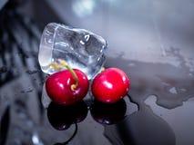Primo piano delle ciliege e del ghiaccio, su fondo nero luminoso Fotografia Stock