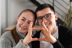 Primo piano delle coppie che fanno forma del cuore con le mani immagini stock