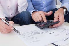 Primo piano delle coppie che fanno le finanze a casa Fotografie Stock