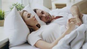 Primo piano delle coppie con i problemi di relazione che hanno conversazione emozionale mentre trovandosi a letto a casa fotografie stock libere da diritti