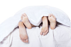 Primo piano delle coppie dei piedi sul letto Immagine Stock Libera da Diritti